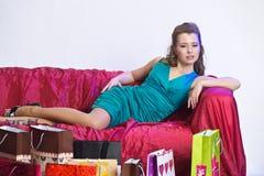 Lycklig och trött kvinna som vilar, når att ha shoppat arkivbilder