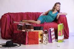 Lycklig och trött kvinna som vilar, når att ha shoppat royaltyfri fotografi