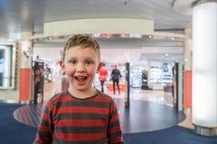 Lycklig och upphetsad pojke framme av ett lager som är ivrigt att gå i shopping royaltyfri fotografi