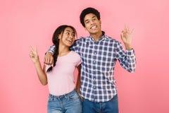 Lycklig ok studentuppvisning och fredgest över rosa bakgrund arkivfoto