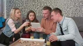 Lycklig olik grupp av vänner som skrattar på vad de ser på skärmen av en datorminnestavla stock video