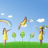 Lycklig påsk! Färgrik bild med ljusa dekorerade ägg, gräs och flickor i gula klänningar Royaltyfri Foto