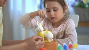 Lycklig påsk! Fostra och hennes lilla dotter med kaninöron som målar påskkaninen arkivfilmer