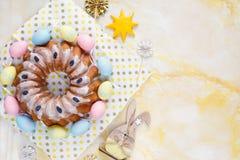 Lycklig påsk! Handgjord kaka på handduken, ägg, träkaninkanin på gulingmarmorbakgrund garnering easter royaltyfri foto