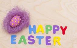 Lycklig påsk och ett rede med ett ägg Arkivbild