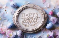 Lycklig påskbakgrund; Blommor för påskägg och vårpå blått t royaltyfria foton