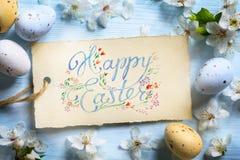 Lycklig påskbakgrund; Vårblommor och easter ägg Arkivfoto