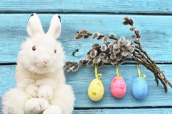 Lycklig påskkanin i korg och ägg på blå bakgrund Royaltyfri Foto