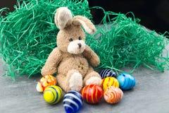 Lycklig påskkanin och kulöra ägg Arkivfoto
