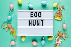 Lycklig påsktext på lightbox på grön pastellfärgad pappers- bakgrund med gula, rosa blåa ägg och den ljusa mallen för kaniner för royaltyfri foto
