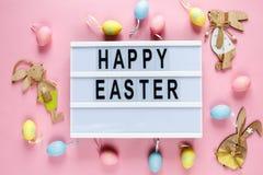 Lycklig påsktext på lightbox på rosa pastellfärgad pappers- bakgrund med gula, rosa blåa ägg och kaniner Ljus mall för påsk royaltyfri bild