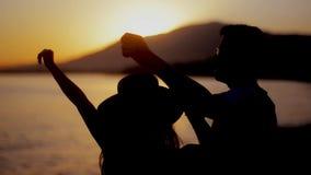 Lycklig pardans på stranden som tycker om bröllopsresa i natur på solnedgången Par som tillsammans tycker om en romantisk solnedg arkivfilmer