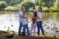 lycklig park för familj Mamman, farsan, sonen och dottern under går i en sommar royaltyfri bild