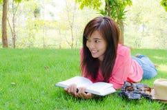 lycklig park för bok som läser den thai kvinnan Royaltyfri Foto