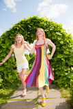 lycklig park som runing två unga kvinnor Arkivfoto