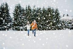 Lycklig parspring i vintersnö royaltyfri bild
