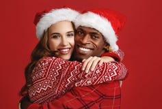Lycklig parsvart man och caucasian kvinna i julhattar på arkivbilder