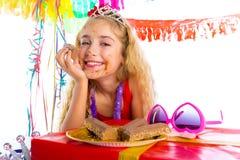 Lycklig partiflicka med gåvor som äter choklad Arkivfoto