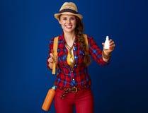 Lycklig passformhandelsresandekvinna som isoleras på nasala droppar för blå visning Royaltyfria Bilder
