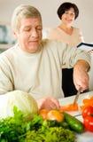 lycklig pensionär för matlagningpar Royaltyfri Bild