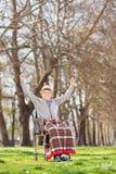Lycklig pensionär i en rullstol som utomhus lyfter hans händer i glädje Royaltyfri Bild