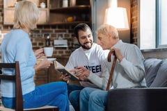 Lycklig pensionär som visar hans favorit- bok till en gladlynt volontär royaltyfri bild