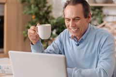 Lycklig pensionerad man som hemma använder den elektroniska grejen arkivfoto