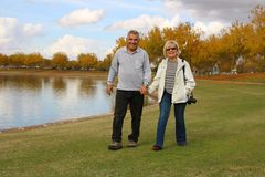 Lycklig pensionär avgick par som går på parkera Royaltyfri Foto