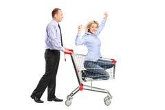 lycklig person för vagn som skjuter shoppingkvinnan royaltyfri fotografi