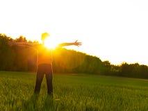 Lycklig person i fältet med lyftta armar på solnedgången royaltyfri fotografi
