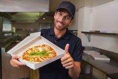 Lycklig pizzaleveransman som visar upp nya pizza och tummar Arkivfoton