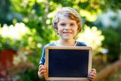 Lycklig pojke för liten unge med kritaskrivbordet i händer Sunt förtjusande för barn tomt skrivbord utomhus för copyspaceinnehav  arkivbild