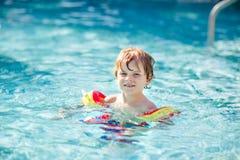 Lycklig pojke för liten unge som har gyckel i en simbassäng Aktivt lyckligt barn som lär att simma med säkra floaties eller swimm arkivbilder