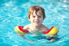Lycklig pojke för liten unge som har gyckel i en simbassäng Aktivt lyckligt förskole- barn som lär att simma med säkra floaties royaltyfri bild