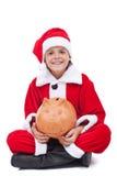 Lycklig pojke i den santa dräkten med spargrisen Arkivbild