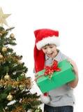 Lycklig pojke i den santa hatten som förvånas vid julgåva Fotografering för Bildbyråer