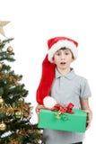 Lycklig pojke i den santa hatten som förvånas vid julgåva Royaltyfria Bilder