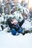 Lycklig pojke i ett lock av Santa Claus i vinterskogen Fotografering för Bildbyråer