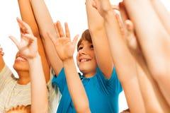 Lycklig pojke i folkmassan med lyfthänder arkivbild