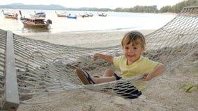 Lycklig pojke i hängmatta på stranden royaltyfria foton
