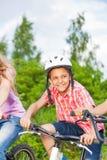 Lycklig pojke i hjälm som rider en cykel Arkivfoton