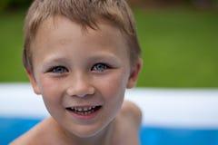 Lycklig pojke i simbassäng royaltyfria foton