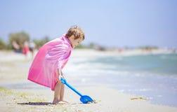 Lycklig pojke i strandhandduken som spelar med skyffeln Royaltyfri Foto