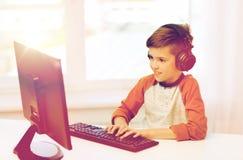 Lycklig pojke med datoren och hörlurar hemma Royaltyfri Foto