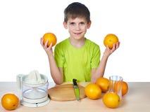 Lycklig pojke med den isolerade apelsiner och juiceren Arkivbild