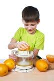 Lycklig pojke med den isolerade apelsiner och juiceren Royaltyfria Foton