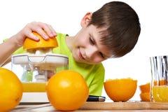 Lycklig pojke med den isolerade apelsiner och juiceren Arkivfoton