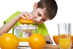 Lycklig pojke med den isolerade apelsiner och juiceren Arkivbilder