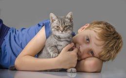 Lycklig pojke med den lilla kattungen Royaltyfri Bild