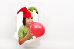 Lycklig pojke med den roliga hatten som firar med en ballong Arkivfoton